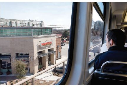 Photo of a man omn a DART train pulling into a station.